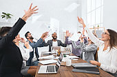 Happy group of business people throw documents