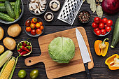 Green cabbage and steel knife on wooden cutting board