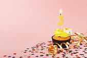 Third birthday cupcake with candle and sprinkles