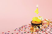 Fourth birthday cupcake with candle and sprinkles