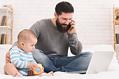 Young dad working on laptop at home with his baby son