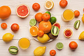Platter of assorted citrus fruits on white wooden planks, top view