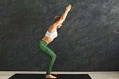 Woman training yoga in chair pose in gym