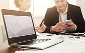 Laptop with financial graph and business meeting