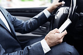 Careless bussinesman driving car and using mobile phone
