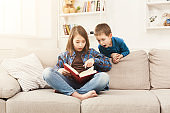 Young girl reading book for her brother
