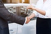 Car saleswoman giving key to new owner