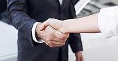 Car sale. Customer and salesman shaking hands