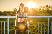 Portrait of sporty slim girl relaxing after sports training outdoors during sunset