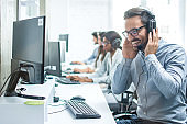 Smiling customer support operator with headphones and microphone working in call center.