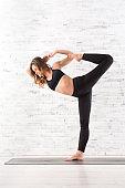 Young fit woman doing natarajasana yoga pose