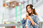 Beautiful young Asian girl listen to music using smartphone and headphone smile at copy space. Modern teenager lifestyle, college student hobby, youth culture or mobile phone gadget technology concept