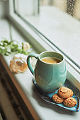 Coffee with amaretto biscuits on a window sill