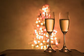 Pair of Champagne glasses next to Christmas tree.