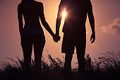 Couple holding hands in the sunset.