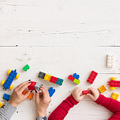 Closeup of young woman's and child's hands playing with toys and plastic bricks on white wooden table background