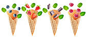 Variation of waffle cones with flying berries and chocolate slices