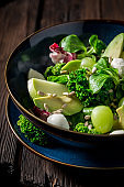 Healthy kale salad with avocado and mix of vegetables