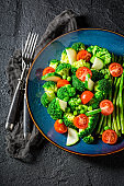 Salad with cherry tomatoes, asparagus and broccoli on black table