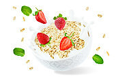 Oat bowl with splash of milk and flying strawberries