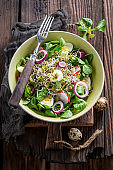 Kale salad with vegetables and avocado on wooden table