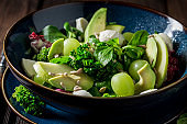 Kale salad with avocado, lettuce and grape in blue bowl