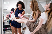 Young women helping their friend to choose sports footwear comparing the soles of new and old shoes in fashion showroom