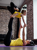 Young woman and little girl doing partner yoga flying pose exercising together
