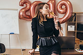Portrait of a young woman in the office drinking champagne.