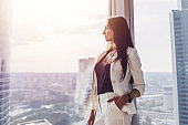 Portrait of elegant business lady wearing white formal suit standing near window looking at cityscape