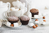 Cups with cacao and marshmallow, cupcakes and different decorations