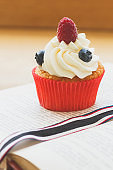 Cupcake with raspberry and blueberry, soft focus background