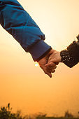 closeup of couple holding hands against sunset sky