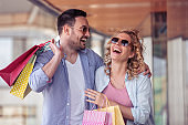 Happy young couple with shopping bags in the city