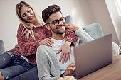 Happy couple relaxing on their couch and using laptop