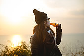young woman drinking beer against sunset sky