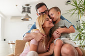 Young parents having fun with their son on bed at home