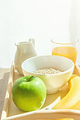 Wooden Tray with Healthy Breakfast Ingredients on Kitchen Table. Oats in Bowl Nut Milk in Pitcher Orange Juice Banana Green Apple. Bright Morning Sunlight Streaming through Window Curtain. Copy Space