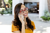 Young woman with eyeglasses laughing at phone