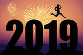 Fireworks at sunset with new year 2019 silhouette and jumping man as symbol for changes