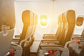 Empty seats in economy class passenger section of airplane near window, Interior of plane with passengers sitting on seat and stewardess walking the aisle in background. Travel concept,vintage color