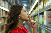 Young woman finger on lips and looking product