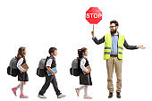 Schoolchildren walking in a line and a teacher with a safety vest and stop sign showing way and looking at the children