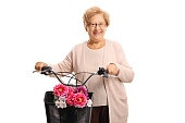 Elderly woman standing with a bicycle