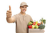 Delivery man with a crate filled with groceries making a thumb up sign