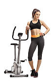 Fitness woman leaning on a stationary bike