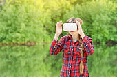 Girl in virtual reality glasses. Greenery of background