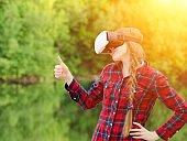 Girl shoots virtual reality glasses, sunset in nature, back view. Thumbs up