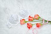White bodice with lace on white fur. Orange roses. Fashionable concept.