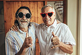 Retired friends with party eyewear giving thumbs up